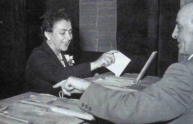 una donna con la veletta inserisce la scheda nell'apposito contenitore