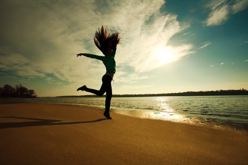 Woman Jumping On The Beach On Sunny Sky Background, Freedom And