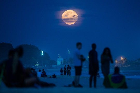 "The full moon, nicknamed ""the supermoon"", rises at Ipanema beach in Rio de Janeiro, Brazil, on August 10, 2014. A supermoon is the coincidence of a full moon or a new moon with the closest approach the Moon makes to the Earth on its elliptical orbit, resulting in the largest apparent size of the lunar disk as seen from Earth. AFP PHOTO / YASUYOSHI CHIBA"