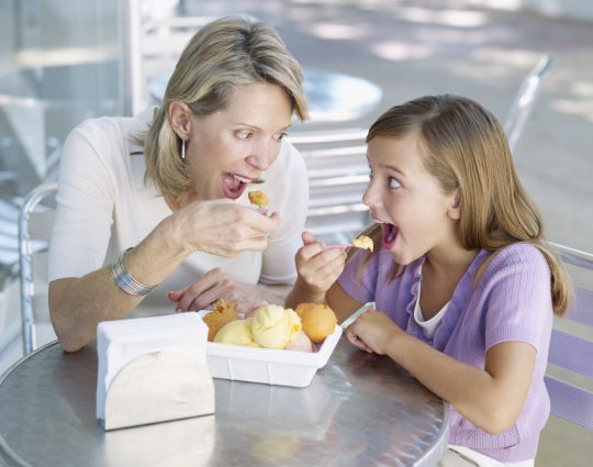 Miami, Florida, USA --- Woman and young girl on outdoor patio eating ice cream --- Image by © Ocean/Corbis